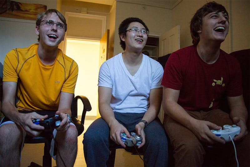"Freshman Jimmy Messmer, left, graduate student Weilin Zou, and senior Tyler Crews play the video game Super Smash Bros. in an Everett dorm room. Inspired by the 2013 film ""Super Smash Bros.,"" members compete against one another in each others dorm rooms, referred to as ""smash houses"" by the group, and in common areas where a television is present."