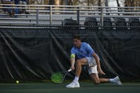 """UNC men's tennis senior Blaine """"Bo"""" Boyden prepares to return the ball during a singles match against NC State on Wednesday April 3, 2019. UNC beat NC State 4-0."""