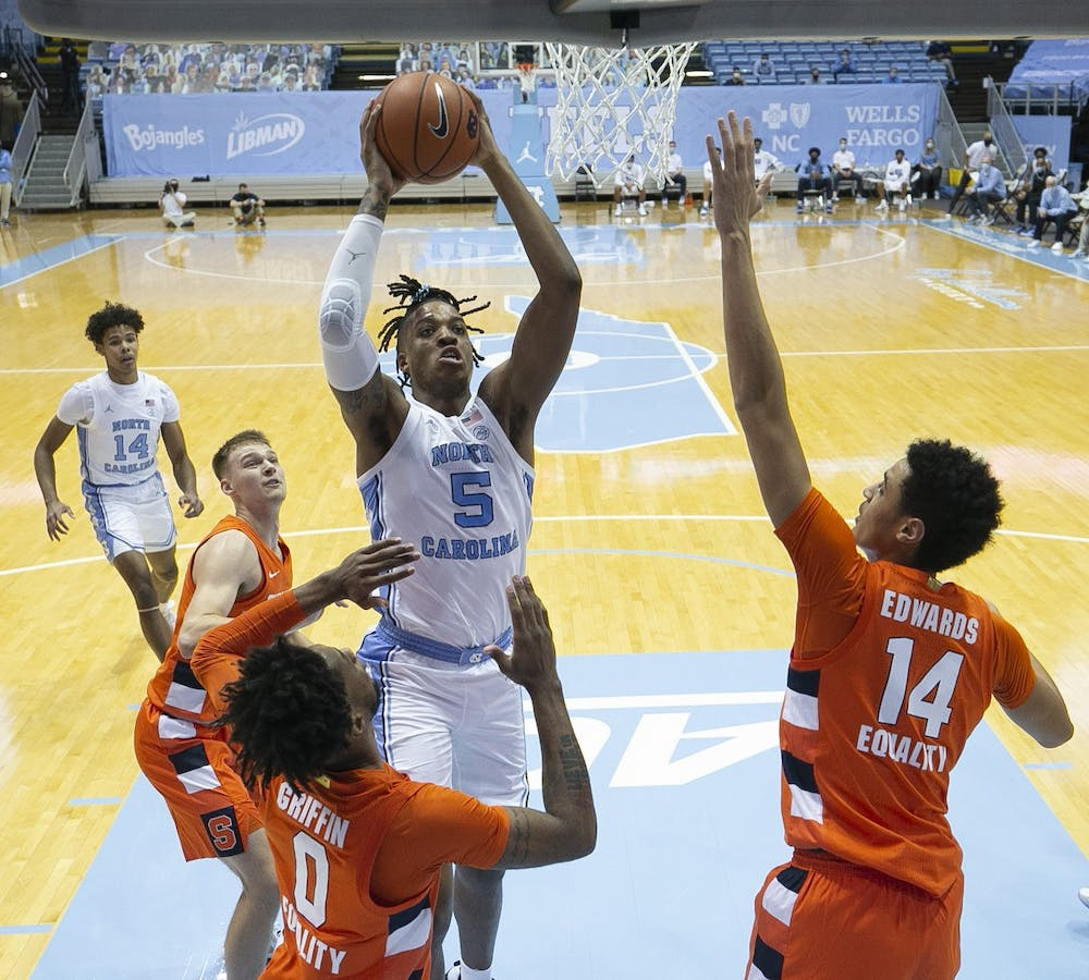 <p>North Carolina's Armando Bacot (5) drives to the basket against Syracuse's Alan Griffin (0) and Jesse Edwards (14) in the first half on Tuesday, January 12, 2021 at the Smith Center in Chapel Hill, NC. Photo courtesy of Robert Willett.</p>