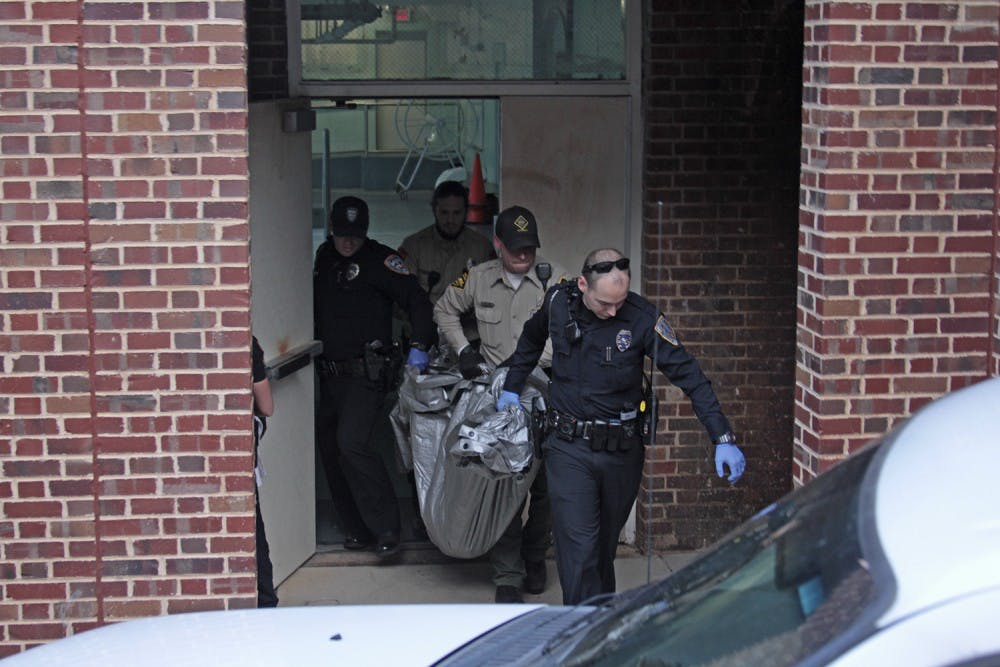 <p>Officials and animal control officers carry the tranquilized deer out of Woollen Gym. The animal broke through a window at Bowman Gray Memorial Pool on Sunday.</p>