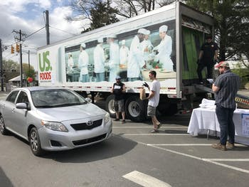 Carrboro United staff, who are all displaced service industry workers, safely deliver food directly to customers' cars on Hub Day at 300 E Main St. in the heart of downtown Carrboro. Photo courtesy of Zoë Dehmer.