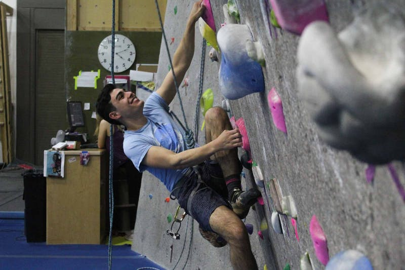 """Bronson Gatts, a sophomore computer science major, warms up at Rock Climbing Club at Fetzer Gym C on Thursday Feb. 27, 2020. """"My favorite part of the club is the community,"""" he said."""
