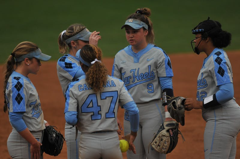 (From left) UNC sophomore short-stop Abby Settlemyre (29) , first-year third baseman Destiny Middleton (47), senior second baseman Campbell Hutcherson (5) and sophomore first baseman Lexi Godwin (9) congratulate George sophomore pitcher Hannah George (42) for striking out Elon's hitter during a game against Elon on Wednesday, Feb. 26, 2020 in G. Anderson Softball Stadium. UNC lost to Elon 2-1.