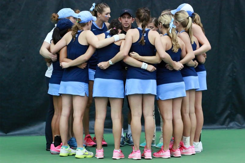 North Carolina women's tennis coach Brian Kalbas talks to the team during their matchup against Duke.