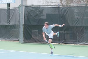 Junior Blaine Boyden follows through on a serve against Wake Forest on March 28 at the Cone-Kenfield Tennis Center.