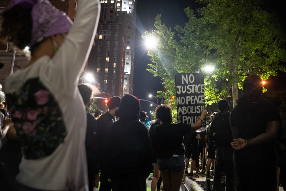 Protestors hold signs in front of the Wake County Courthouse in downtown Raleigh during the Black Lives Matter protest on Friday, Aug. 28, 2020.