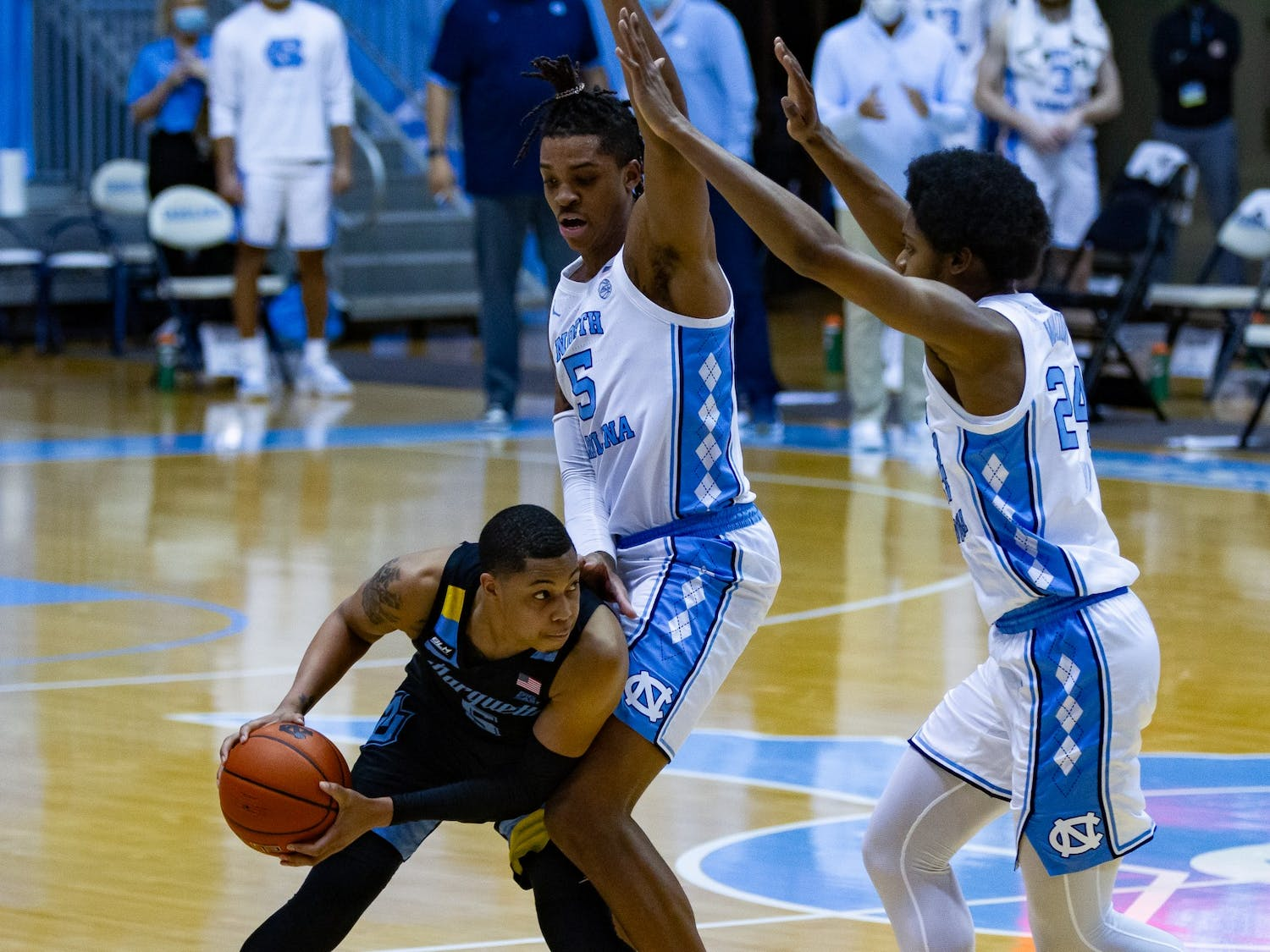 UNC sophomore center Armando Bacot (5) and first year guard Kerwin Walton (24) attempt to defend against Marquette redshirt junior guard Greg Elliot (5) during a game in the Smith Center on Wednesday, Feb. 24, 202. UNC lost to Marquette 83-70.