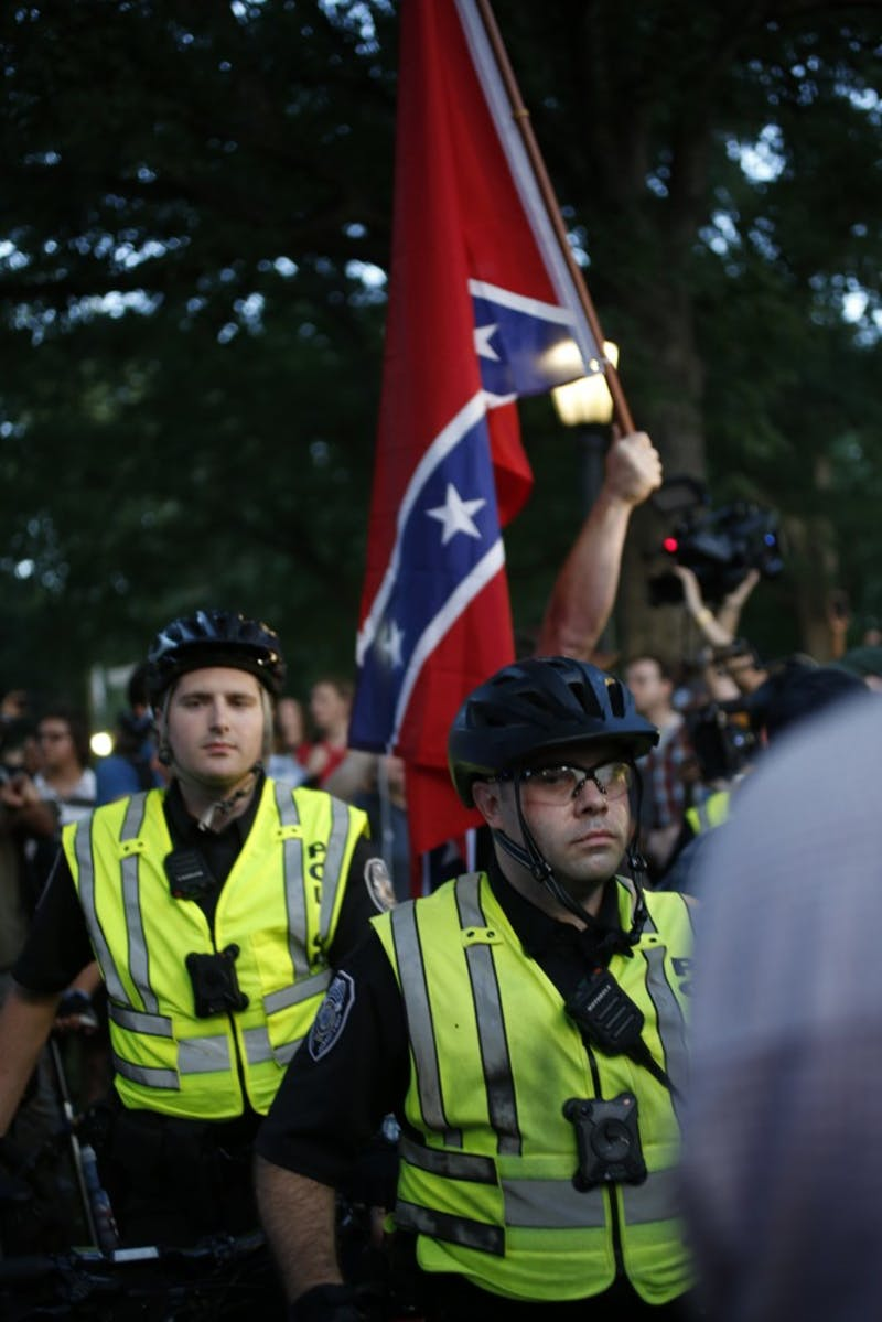 Police form a barricade as one of the demonstrators enters McCorkle Place carrying a Confederate flag on Thursday night.