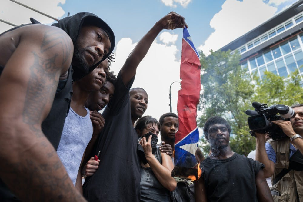 <p>Counter-protestors burn a Confederate flag in anticipation of a KKK rally in Durham.</p>