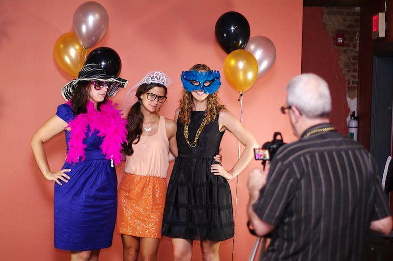 From left to right, Laura Houston, a UNC grad student from Long Island, NY, Claire Dennis, a therapist from Durham, and Colie Taico, the hostess of the event, from Chapel Hill, dress up for the photo booth at 2nd Chance Prom at Looking Glass Cafe on Saturday.