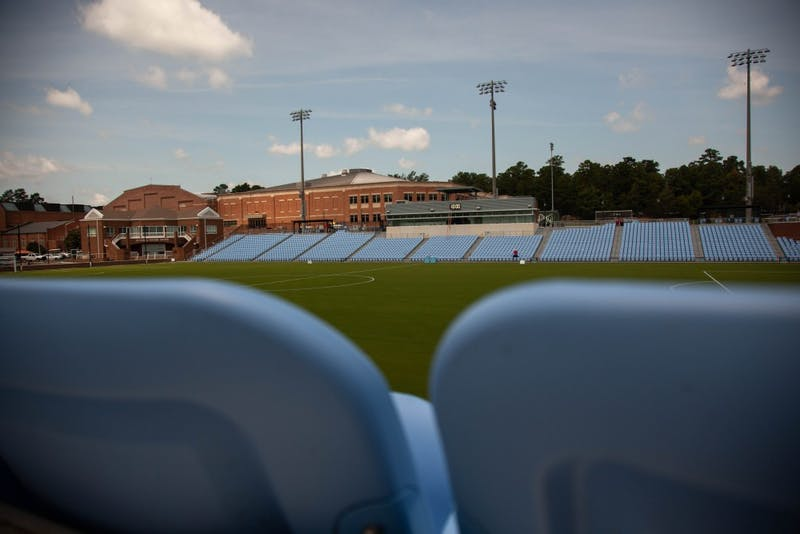 The UNC Soccer Stadium features hard-backed seats throughout the area. The stadium sits behind Hooker fields and adjacent to the Eddie Smith Field House.