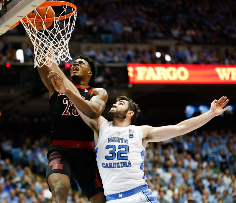 UNC senior forward Luke Maye (32) tries to block Louisville center Steven Enoch (23) as he shoots the ball in the Smith Center Saturday, Jan. 12, 2019. Lousivlle beat UNC 83-62.
