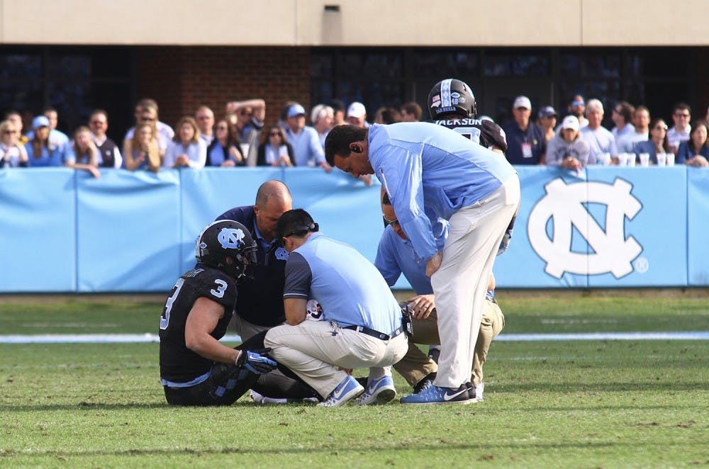 <p>Senior Ryan Switzer (3) is looked at on the field after a minor injury in the game Friday against N.C. State.&nbsp;</p>