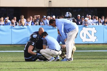 Senior Ryan Switzer (3) is looked at on the field after a minor injury in the game Friday against N.C. State.