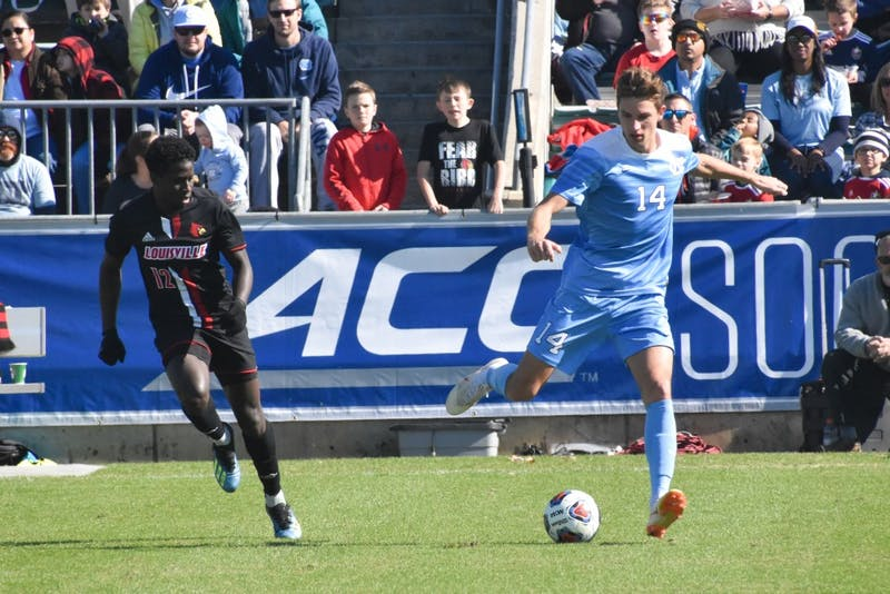 Louisville midfielder Cherif Dieye (12) races after UNC senior Nils Bruening (14) in the ACC championship game on Sunday, Nov. 11, 2018 at WakeMed Soccer Park. UNC lost to Louisville 0-1.