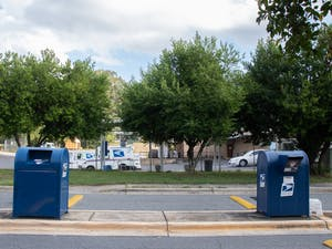 Two USPS collection boxes sit in front of a USPS mail truck parking lot on Sept. 26, 2020 in Matthews, NC.