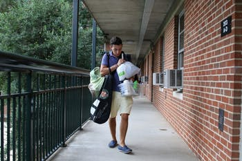 First year Albert Bell from Miami carries personal items towards his room in Hinton James on move in day.