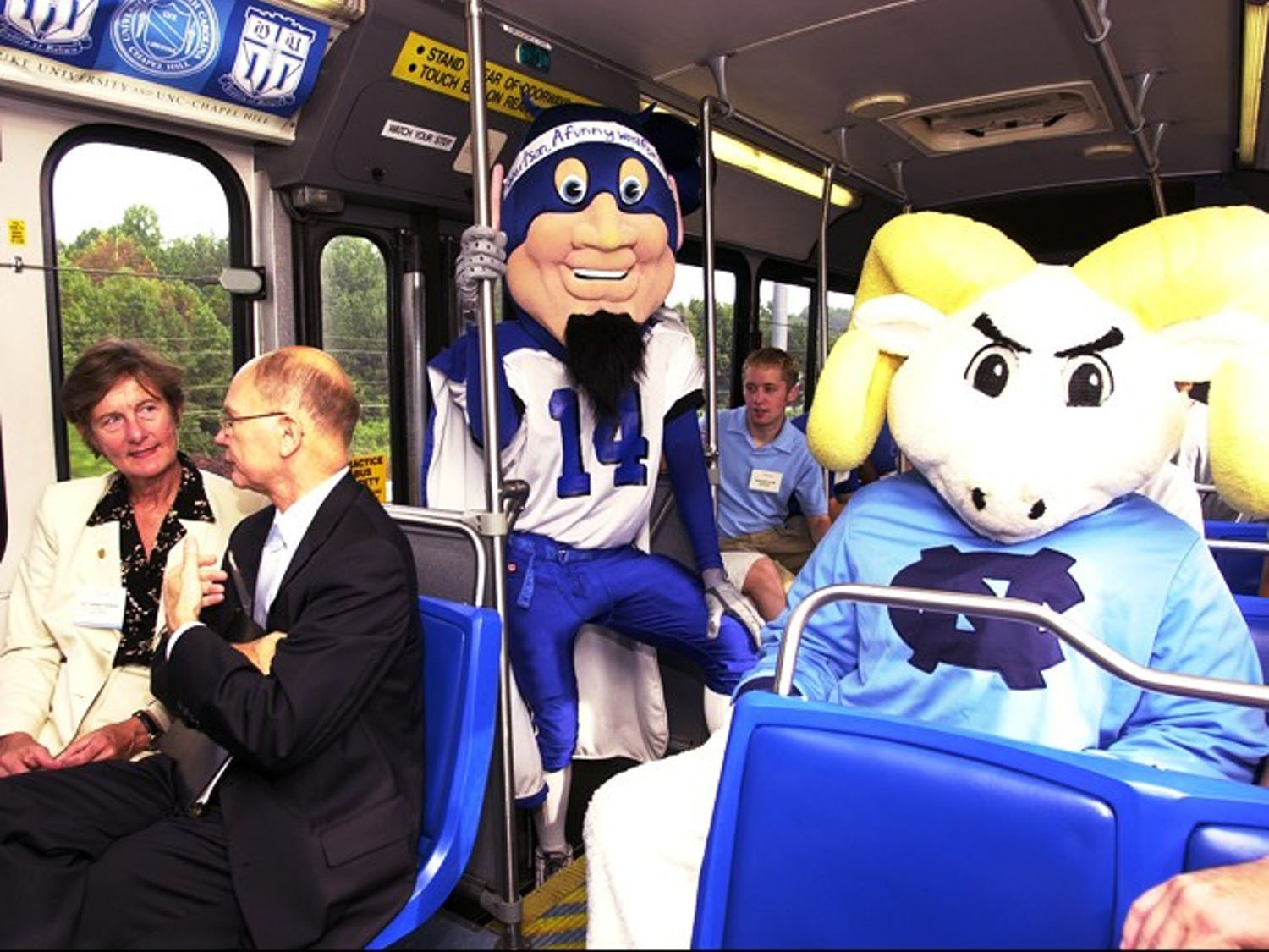 Former UNC Chancellor James Moeser rides with former Duke President Nannerl Keohane on the Robertson Bus on its inaugural trip in 2001.  Courtesy of UNC News Services/Dan Sears