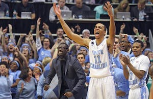 Theo Pinson (left) and Brice Johnson (11) celebrate from the bench on Feb. 24.