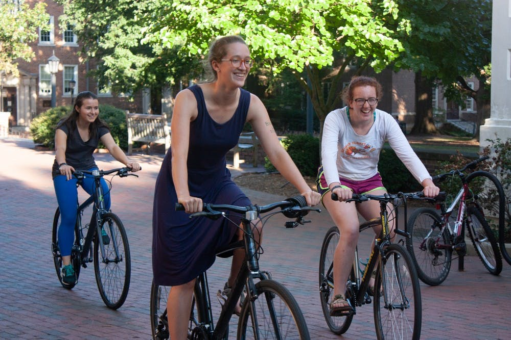 (From left) Junior Brooke Bauman, an environmental science major, senior Evelyn Morris, an economics major and senior Megan Raisle, a geography and environmental studies major, bike outside the Campus Y during a sign-making event on Thursday, Sept. 19, 2019. They will participate in the Triangle Climate Strike on Friday. Raisle will lead the bike ride from Chapel Hill to the location of the strike. The event is part of a global protest calling for action toward climate change. Participants are encouraged to bike, walk, or use other environmentally-friendly methods to go to the event.