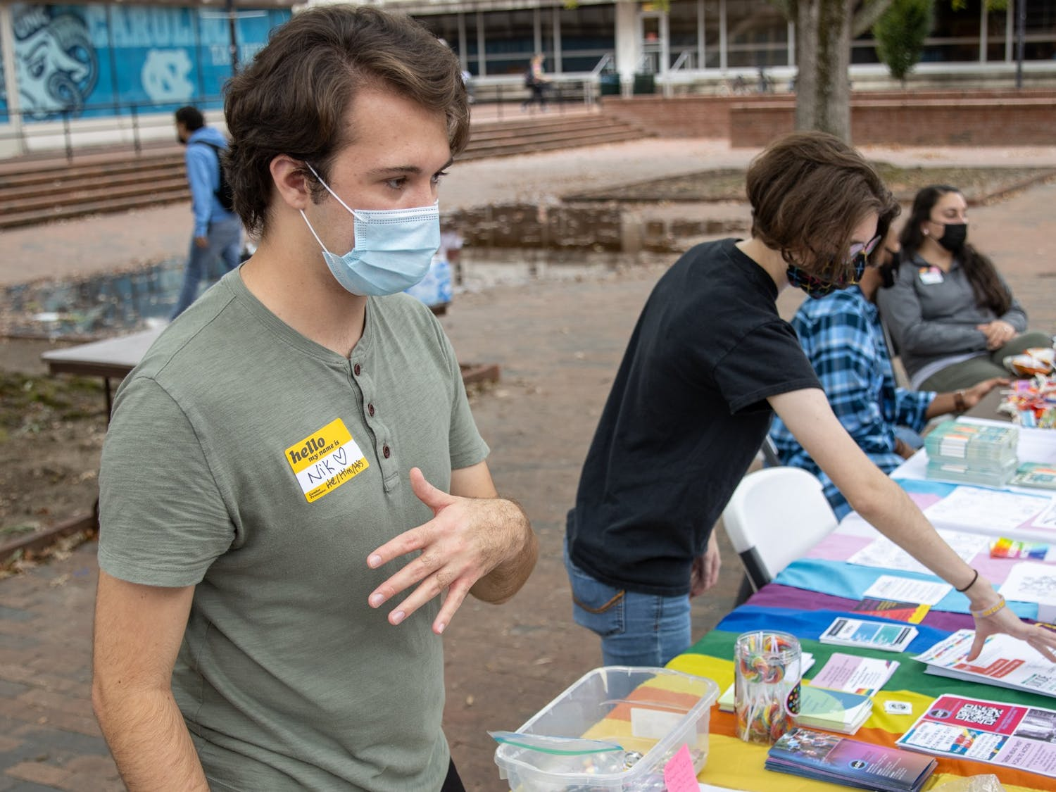 Junior environmental studies major Nikalus Ward and senior biology major Rowan Merritt talk to patrons that visited the coming-out-day table in the Pit on Oct. 11. The event was sponsored by UNC's LGBTQ Center.