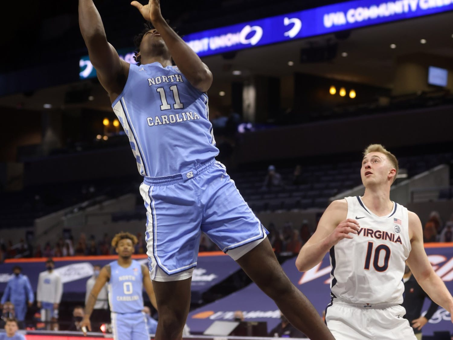 North Carolina forward Day'Ron Sharpe (11) shoots next to Virginia forward Sam Hauser (10) during the game Saturday in Charlottesville. Photo courtesy of Andrew Shurtleff/The Daily Progress.