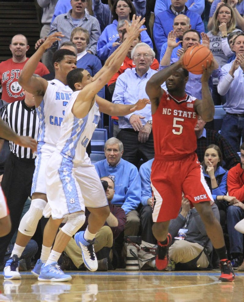 Marcus Paige (5) and Kennedy Meeks (3) double up on NC State's Desmond Lee (5).