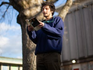 Ben Goldman, a former UNC student, reads poetry in the Pit on Monday, Jan. 18, 2021. Goldman is pictured here reading works by Billy Collins.