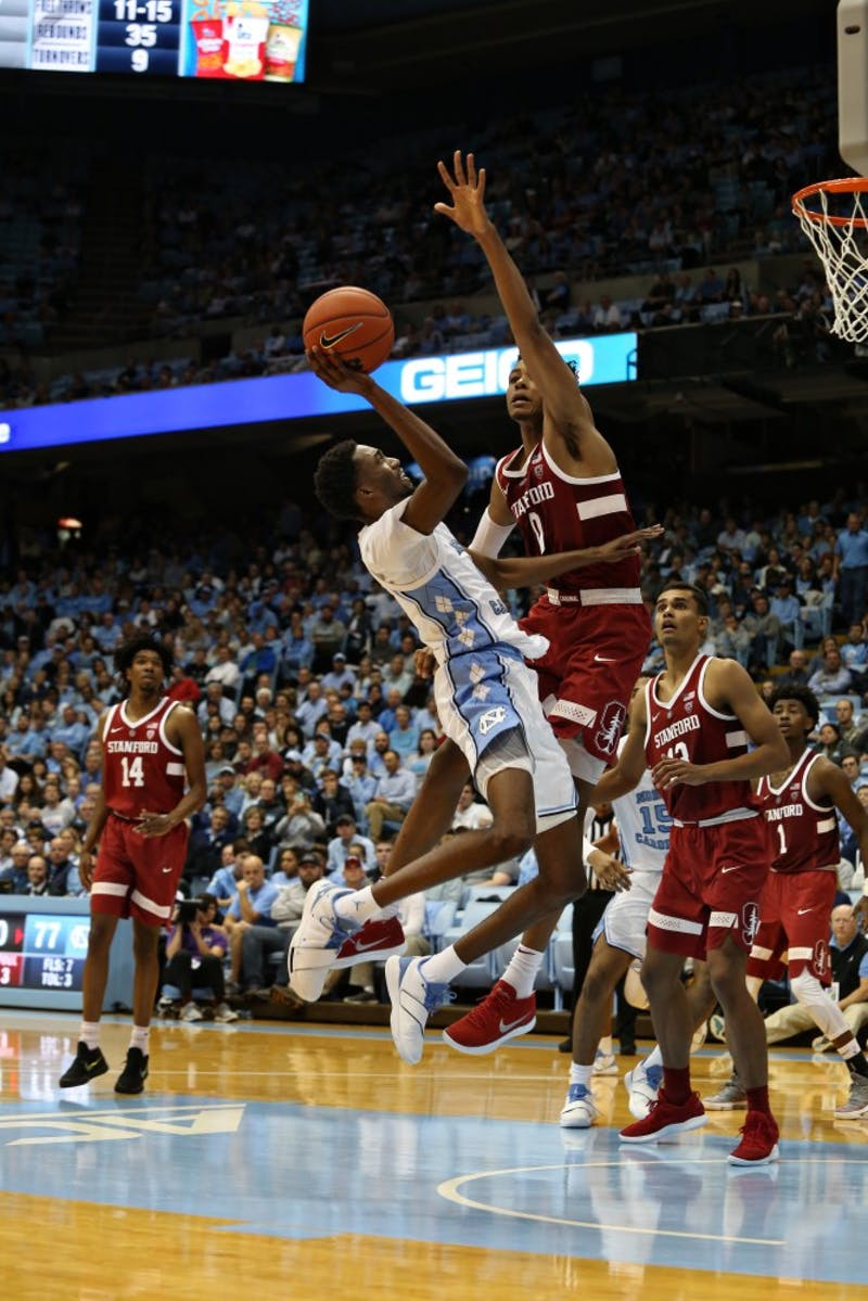 UNC guard Brandon Robinson (4) pulls up for a shot while guarded by Stanford forward KZ Okpala (0) in the Dean Smith Center on Monday, Nov. 12, 2018