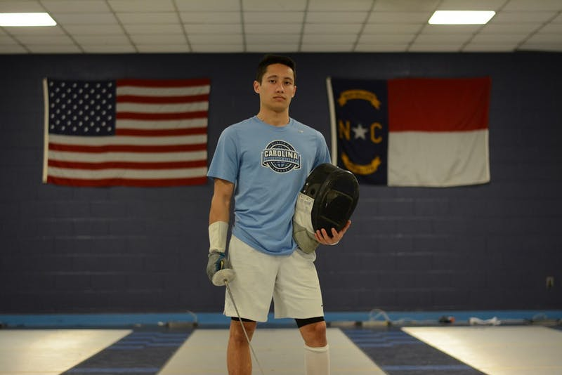 Ezra Baeli-Wang poses with his gear in the fencing room in 2017. The former UNC and ACC Student-Athlete Advisory Committee President wrote an open letter to University officials against Silent Sam that has been signed by more than 270 current and former UNC student-athletes.