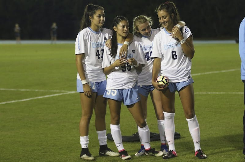 UNC midfielder Abby Elinsky (8) is embraced by her teammates Alex Kimball (47), Jenny Chiu (95) and Cannon Clough (49) before the start of Thursday night's game against Florida State. Elinsky lost her older brother, Nick, on October 2nd.