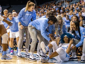 The UNC women's basketball team celebrates redshirt senior guard Madinah Muhammed (3) after she fell for a shot. The Tar Heels beat the Tigers 86-72 on Sunday, Feb. 2, 2020 in Carmichael Arena.