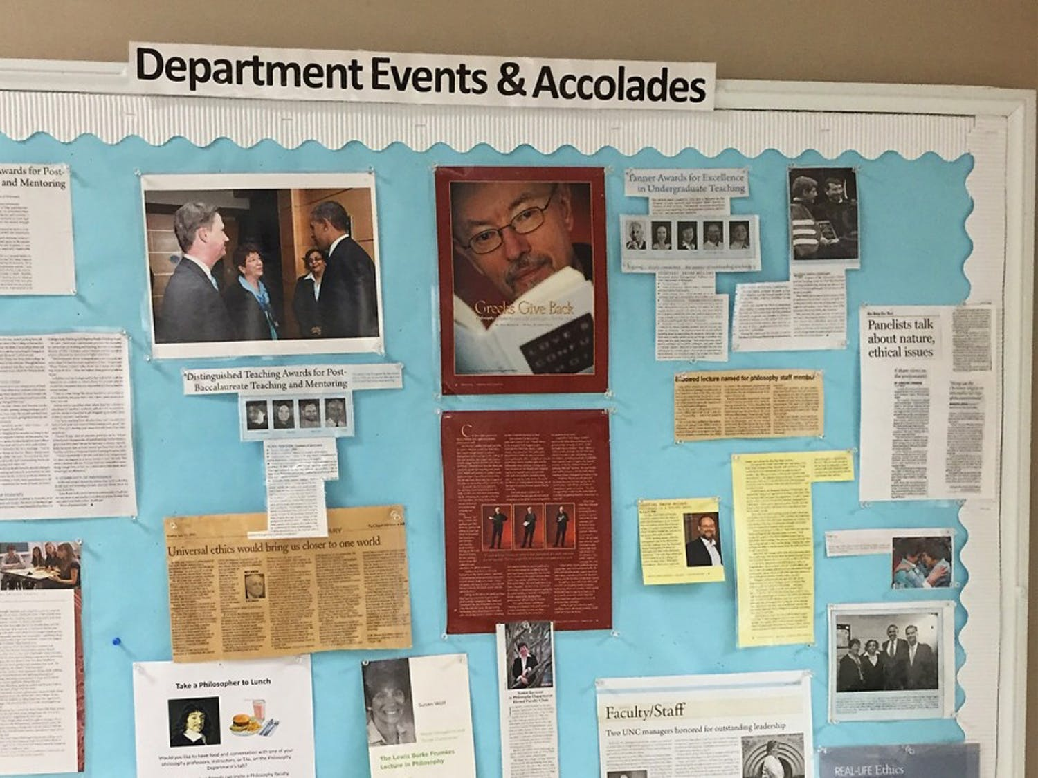 Jan Boxill is featured with Chancellor Folt and President Obama on a bulletin board in Caldwell Hall celebrating philosophy professors' work.