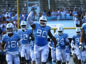 Nazair Jones (90) holds up a chain as the team walks out of the tunnel at the beginning of the game against Pitt.