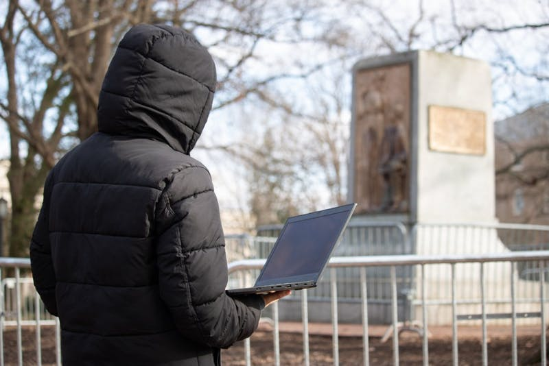DTH PHOTO ILLUSTRATION. A student faces the pedestal of Silent Sam as they hold and view a laptop. Annie Simpson (not pictured) seeks legal counsel to take action against UNC for the removal of her websites, regarding Silent Sam, from the Board of Governors and UNC's servers.