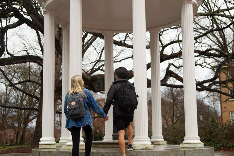 DTH Photo Illustration. A UNC Couple holds hands in front of the Old Well on Thursday, Feb. 13, 2020. Many couples will be celebrating Valentine's Day together and are reflecting on how they met on UNC's campus.