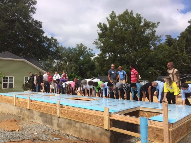 Community members gather to raise a wall to commemorate the accomplishments made during the first year of the Northside Neighborhood Initiative. Photo courtesy of Sally Bitar.