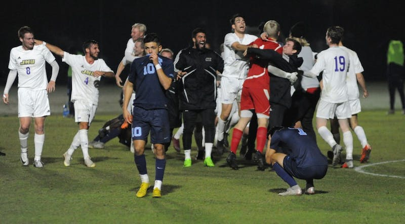 James Madison celebrates winning Sunday's NCAA tournament game at WakeMed Soccer park as UNC players leave the field.