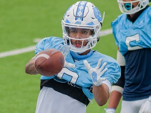 Sophomore wide receiver Emory Simmons (0) catches the ball during a drill at the football practice on Saturday Mar. 27, 2021 at Kenan Stadium.