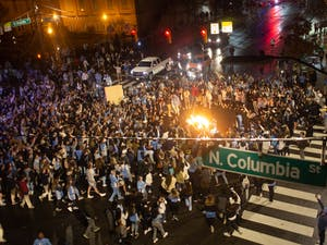 Students rush Franklin Street after the Tar Heels defeat the Blue Devils despite COVID-19 restrictions.