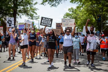 Niya Fearrington (left) and Victoria Fornville (right) lead the crowd at the Chapel Hill Rally for Justice in June. Photo courtesy of Dakota Moyer at Chapelboro.com.