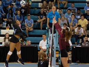 Redshirt first-year outside hitter Lauren Harrison (25) spikes the ball against two players from FSU. UNC won against FSU 3-2 at Carmichael Arena on Sunday, Oct. 13, 2019.