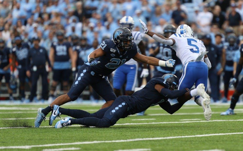Junior linebacker Chazz Surratt (21) and senior defensive back Myles Dorn (1) take down Duke's Jalon Calhoun (5) in Kenan Memorial Stadium on Saturday, Oct. 26, 2019. UNC defeated Duke 20-17.