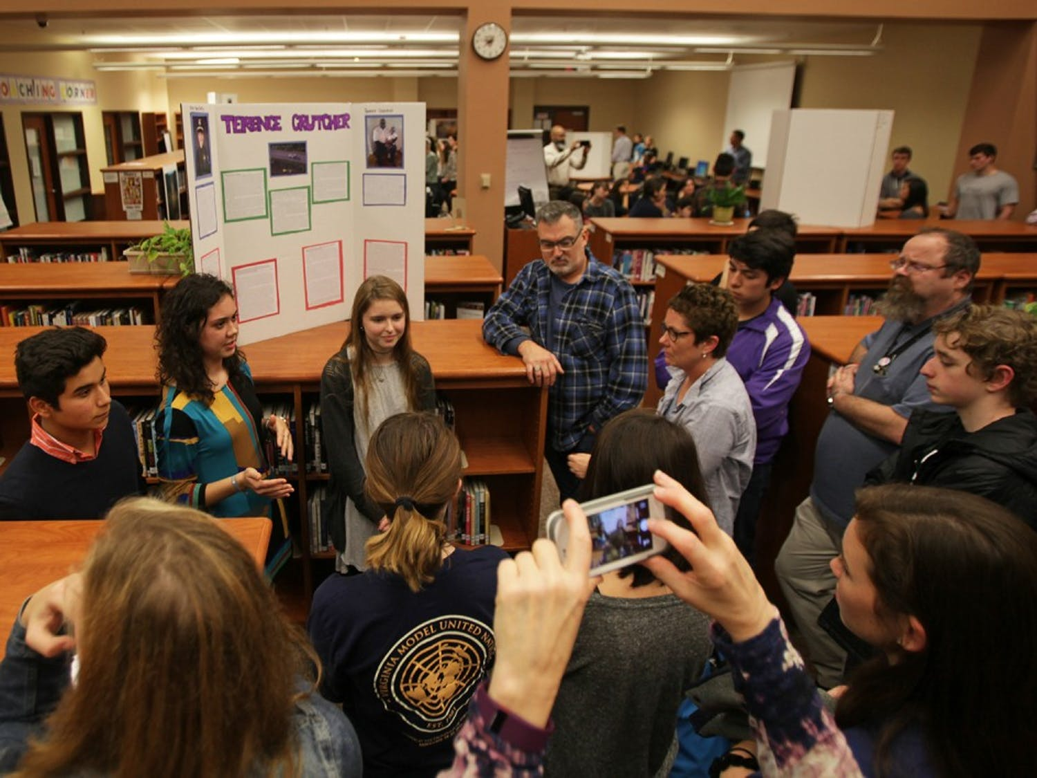 Carrboro High School students (from left) Amado Ruiz-Perez, Sophie Therber and Lily Ervin, give a presentation on Terence Crutcher, one of many victims of recent police shootings Tuesday evening.