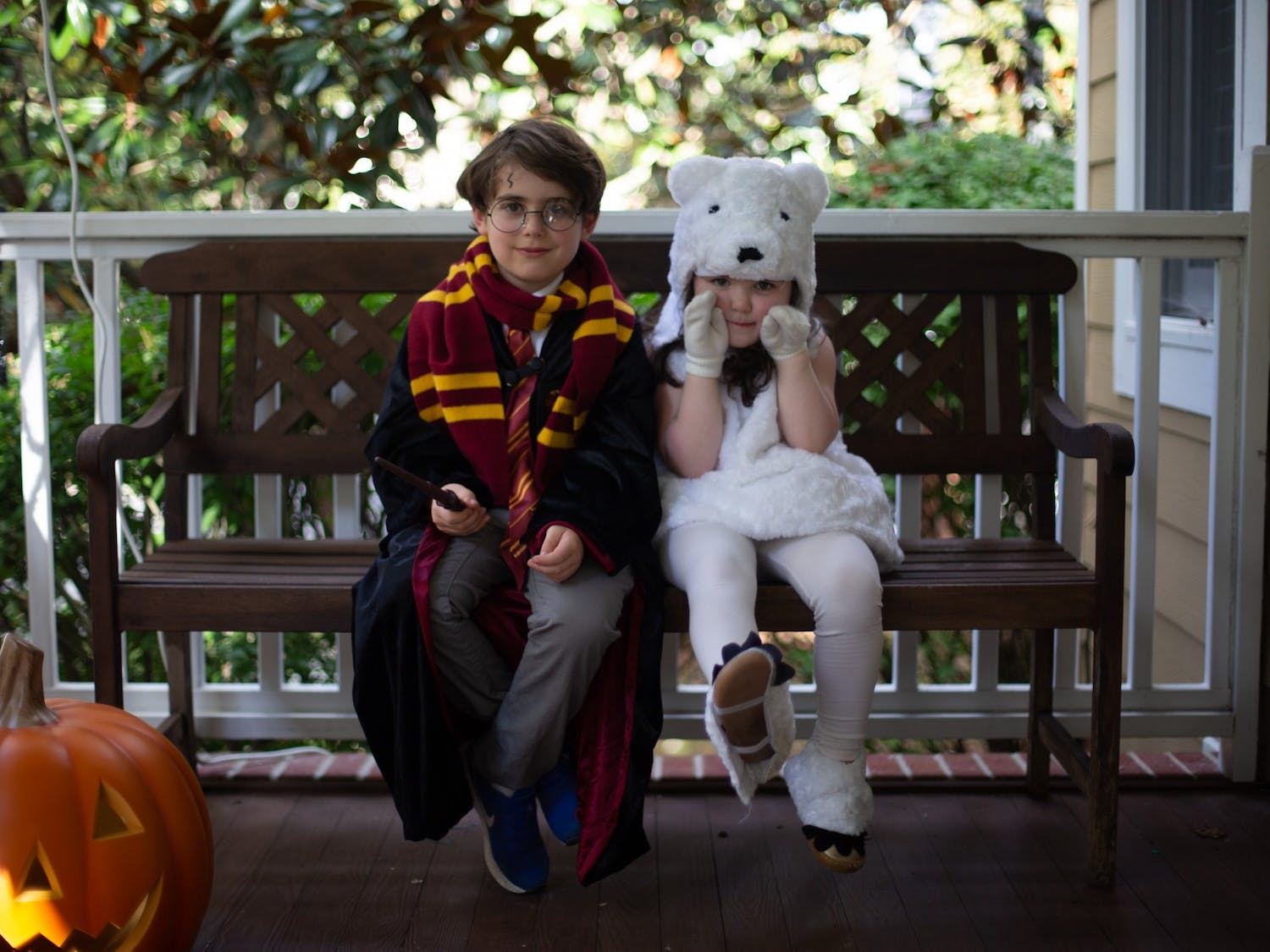 Blake, 7, and Lila, 4, pose for a portrait on their front porch. Blake is dressed as Harry Potter and Lila is dressed as a polar bear.