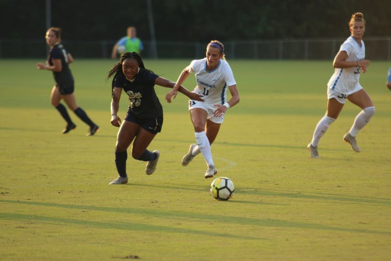 Defender Emily Fox  (11) and Pittsburgh Forward Ari Morgan (26) race toward the ball at Wakemed Soccer Park in Cary, NC on Thursday evening.
