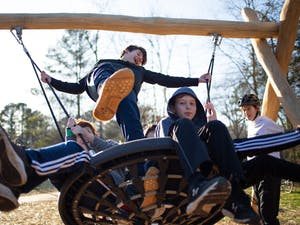 (From left) Josh Delaney, 12, Ben Dover, 13, and Connor Pants, 10, swing as Dexter McQueen, 12, looks on at the recently opened Martin Luther King Jr. Park on Monday, Jan. 20, 2020. Members of the community gathered for the park's ribbon-cutting two years after the initial groundbreaking.