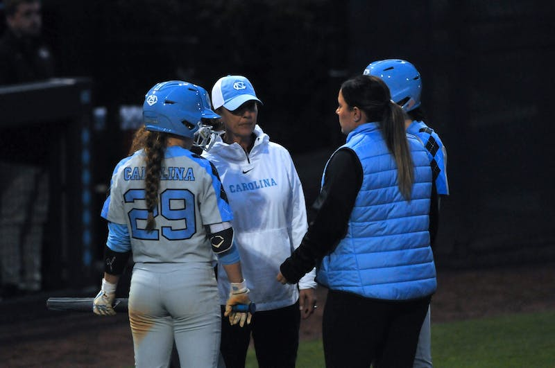 (From left) UNC Sophomore Abby Settlemyre (29), Coach Mary Jo Firnbach, and Coach Chelsey Dobbins gather to talk about the inning during a game against Elon on Wednesday, Feb. 26, 2020 in G. Anderson Softball Stadium. UNC lost to Elon 2-1.