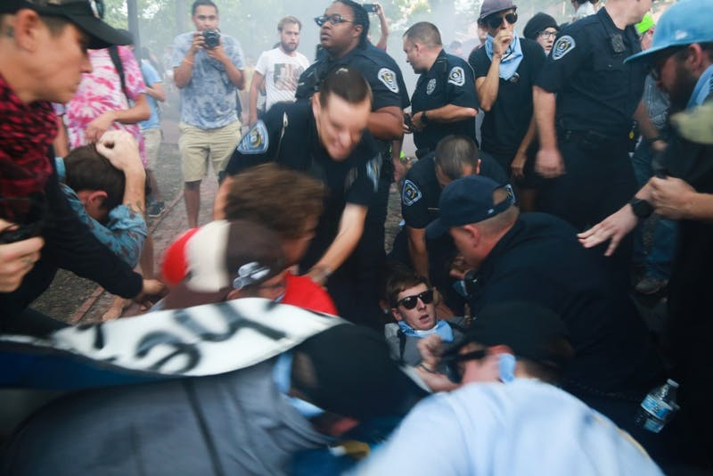 UNC Department of Public Safety officers hold down a protestor.