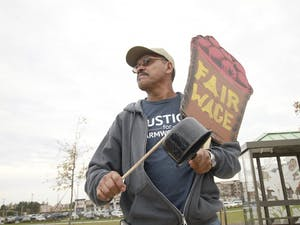 CIW farmer Santiago Perez holds signs in protest at the Cary Publix. The workers are fighting for fairer wages and produce prices.